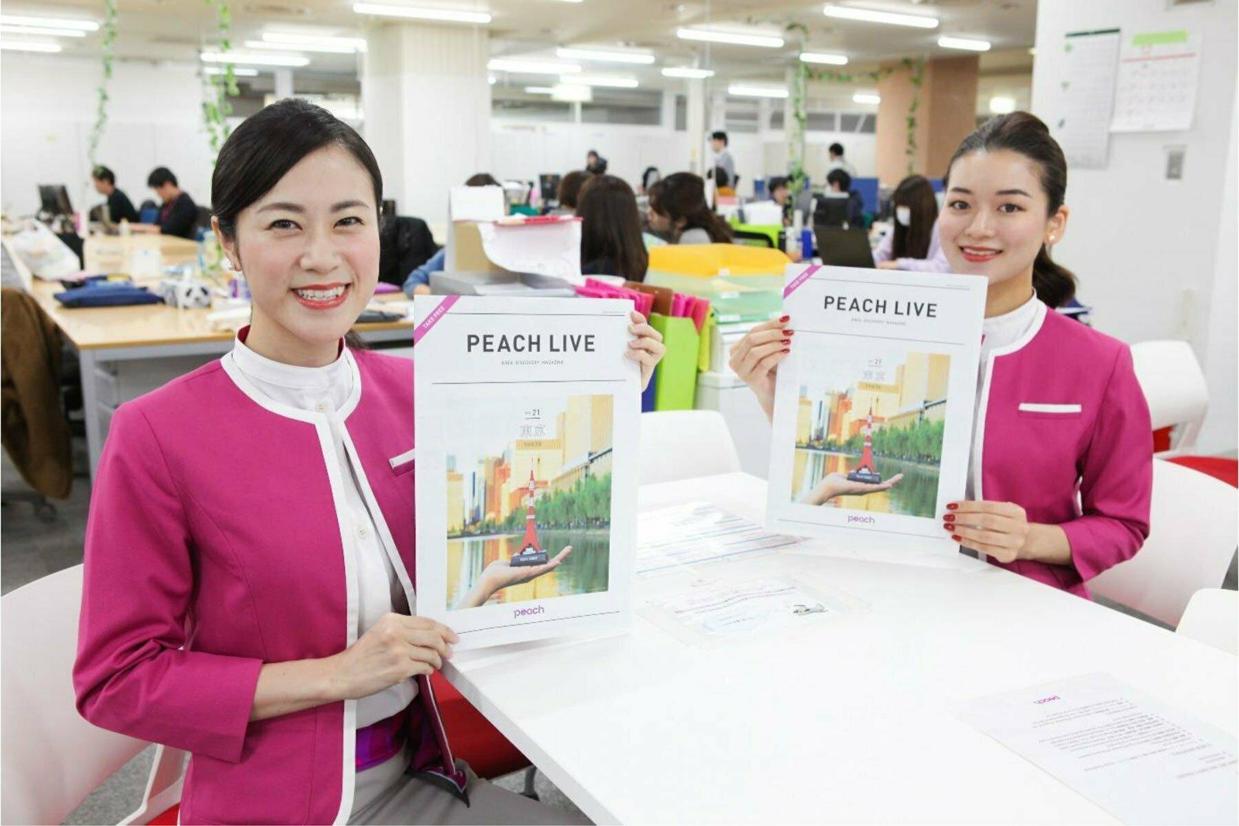 Peach Live Tokyo を手に持つキャビンアテンダント